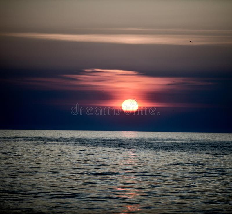 A Rising Sun Through Marine Layer #3. This is an early morning Summer picture of a rising sun through the marine layer on Lake Michigan off Diversey Harbor stock image