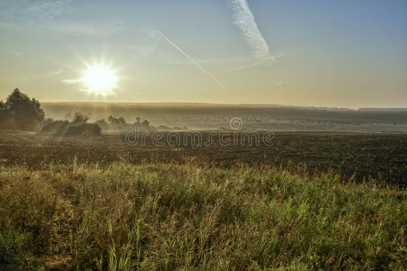 Rising sun over the field, sun rays, vegetation and trees, buildings. A trail in the sky from an airplane flying at height stock photos
