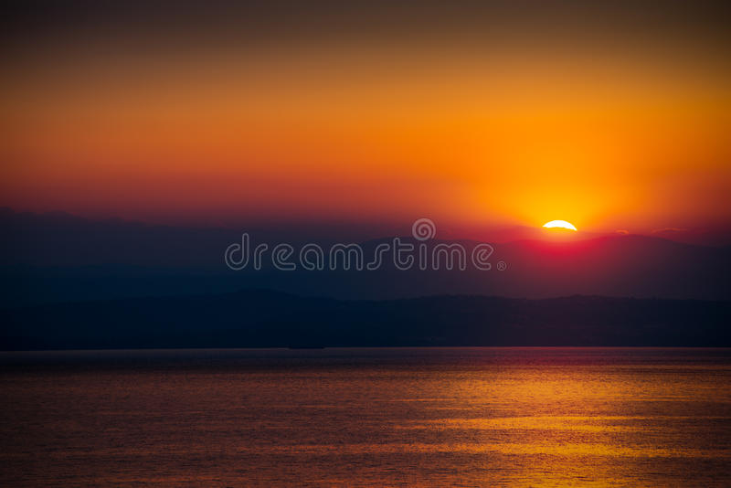 The Rising Sun. Over the Sea with Beautiful Vibrant Red Glow. Mountains in Background stock photos
