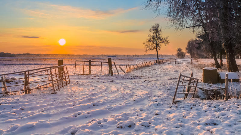 Rising sun over Winter Landscape. With Snowy Fields and Blue Sky in Drenthe Netherlands stock photos
