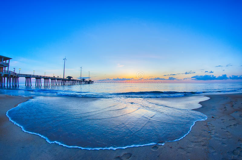 The rising sun peeks through clouds and is reflected in waves by. The Nags Head fishing pier on the outer banks of North Carolina stock photos
