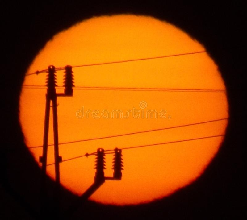 The rising sun. Of power lines against a rising sun royalty free stock photography