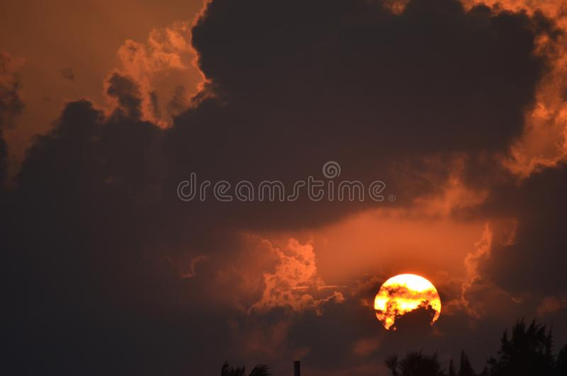 The rising sun seen against grey clouds and an orange sky. The orb of the rising sun burns white and gold against an orange sky. Dark clouds fill the sky stock image