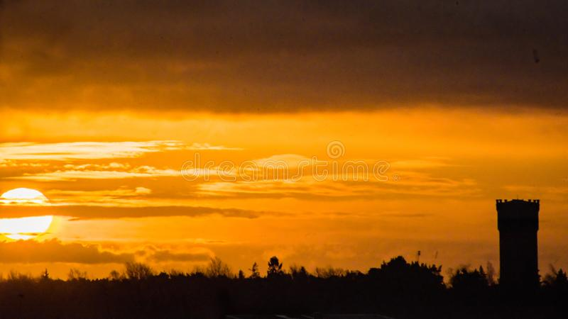 Rising sun tower. Rising sun with tower to the right. Yellow picture stock image
