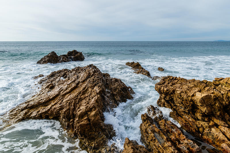 Rising surf breaking on rocky California shore royalty free stock photo