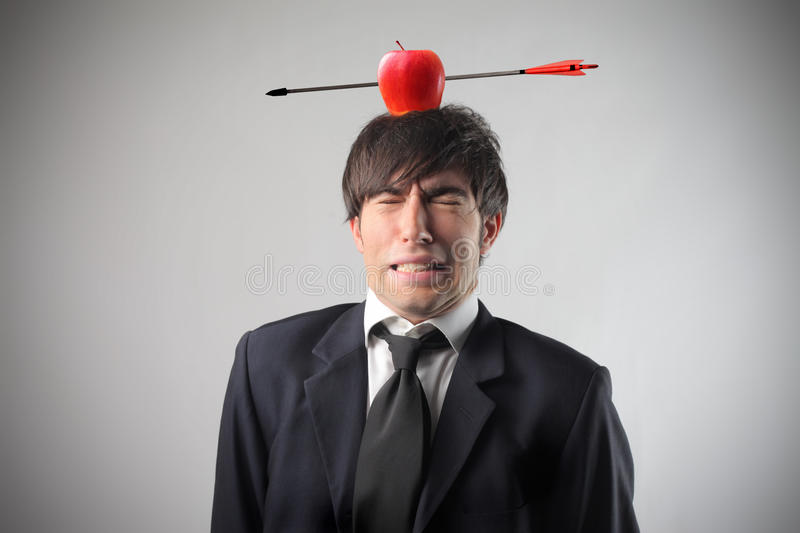 Risk. Portrait of a worried businessman with a red apple pierced by an arrow on his head stock image