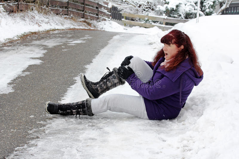 Risk of accidents in winter. A woman slipped on a slippery road and snow has pain stock photography