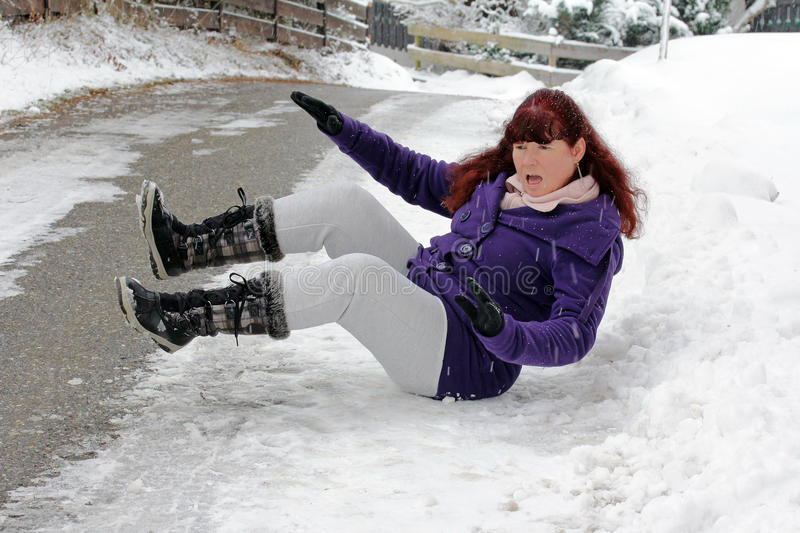 Risk of accidents in winter. A woman slipped on a snow slippery road stock photos