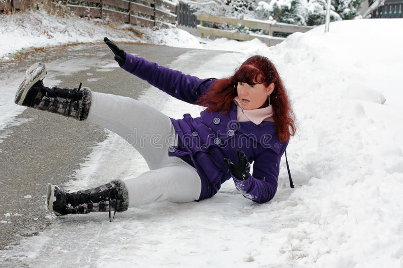Risk of accidents in winter. A woman slipped on a snow slippery road stock photography