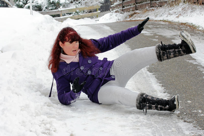 Risk of accidents in winter. A woman slipped on a snow slippery road royalty free stock image