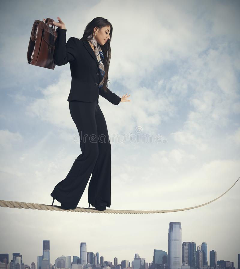 Risk in business. Concept of risk in business with businesswoman on the rope royalty free stock photo