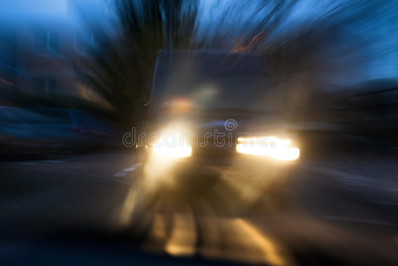Risk of car accident. A van approaching in a menacing way in twilight, with deliberate camera shake for the concept of car accident risks stock image