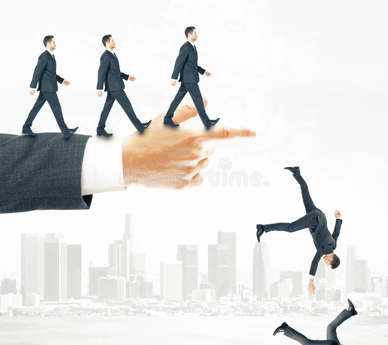 Risk and failure concept. Abstract image of businessmen walking and falling off pointing hand on city background. Risk and failure concept stock images