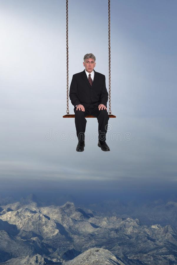 Risk Management, Business, Sales, Marketing, Surreal Businessman. A surreal businessman sits in a swing above mountains in the sky. Abstract concept for jobs stock image