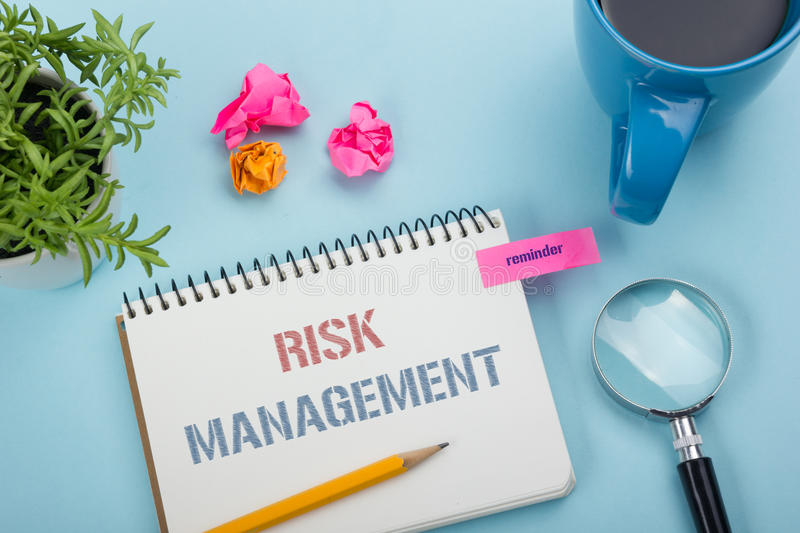 Risk Management concept. Notepad with message, pencil and flower, coffe cup. Office supplies on desk table top view royalty free stock photography