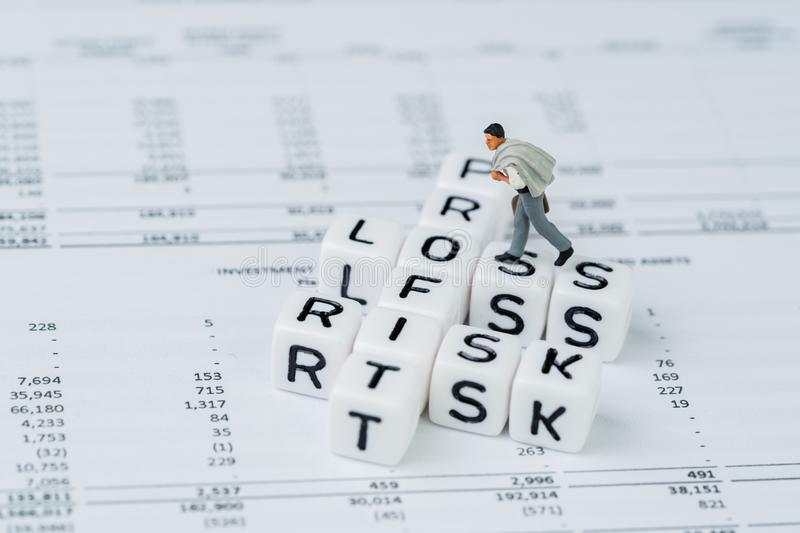 Risk, profit and loss in investment concept, miniature businessman walking on small white cube block with alphabet with crossword. Word mainly as Profit, Loss stock image