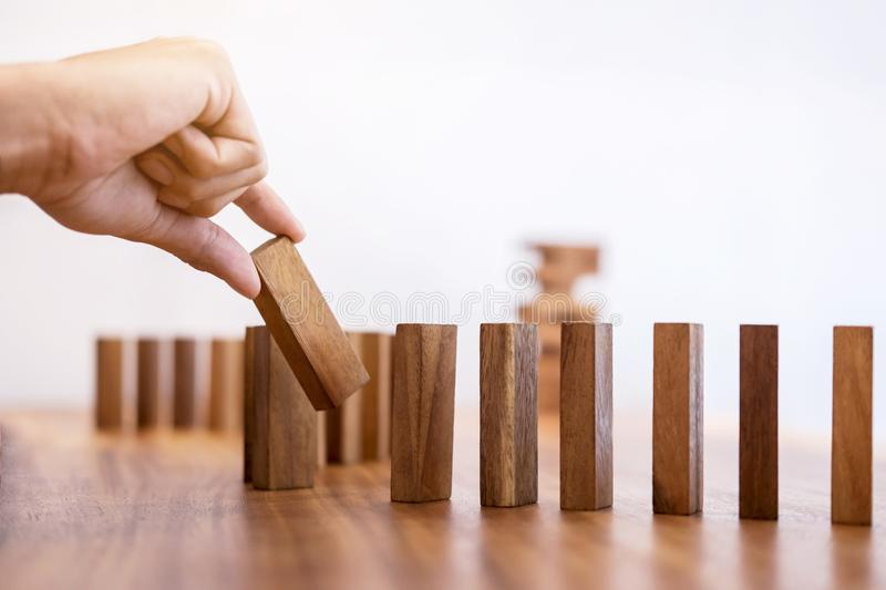 Risk and strategy in business, Close up of businessman hand gambling placing wooden block on a line of domino royalty free stock image