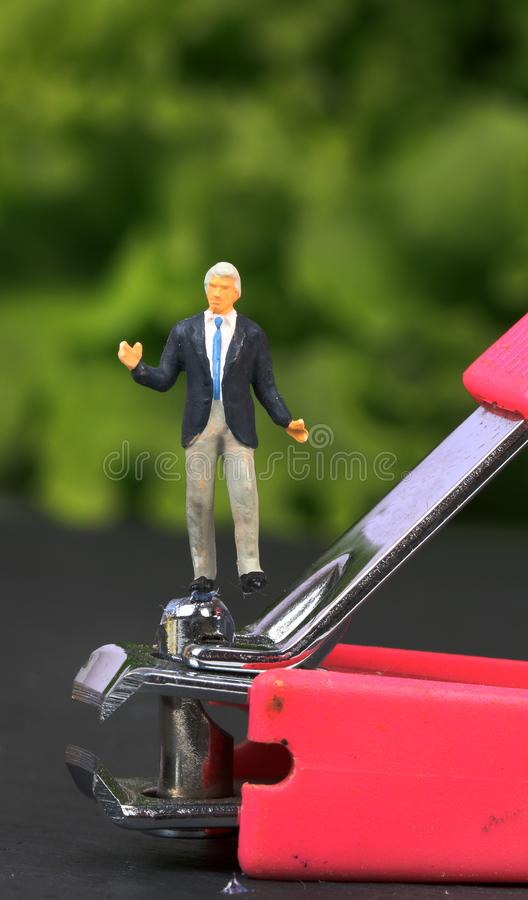 Risk taker. Concept shot showing male man standing on nail cutter royalty free stock images