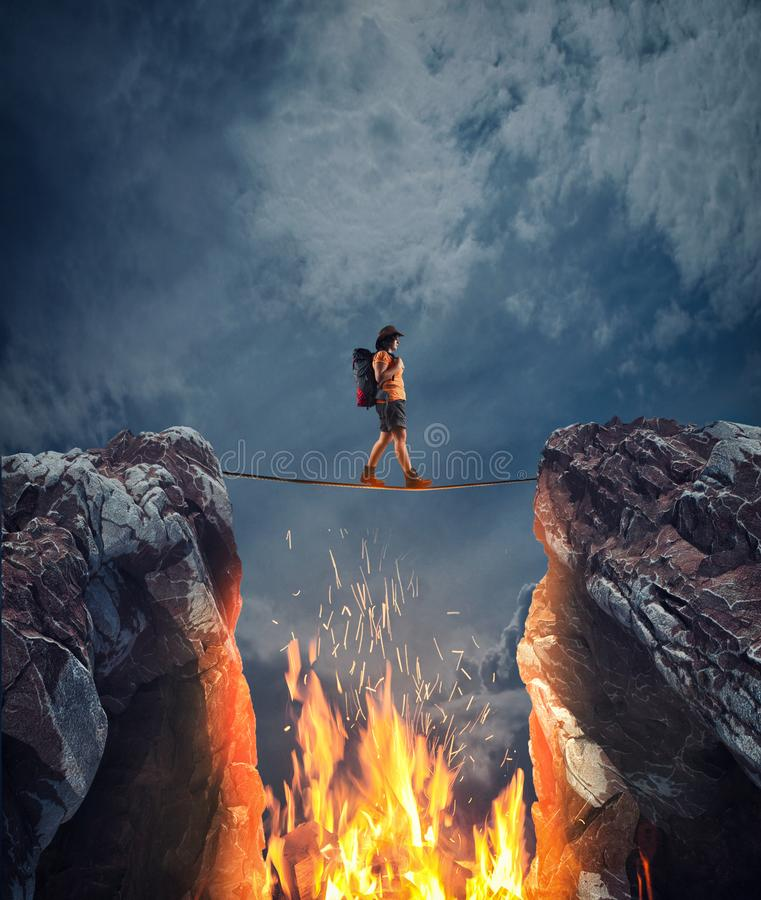 Risk taking concept. Surreal challenge overcome . Woman conquering obstacle balancing on slackline rope above a gap with flames between two mountain peaks.Risk stock image