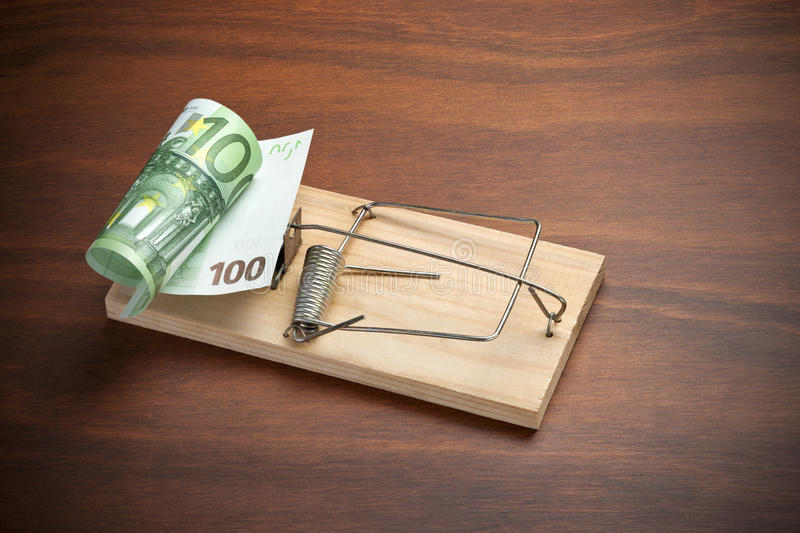 Risk Trap Investment Money Euro. A conceptual image of a one hundred euro note set in a mouse or rat trap on a wood background stock photo