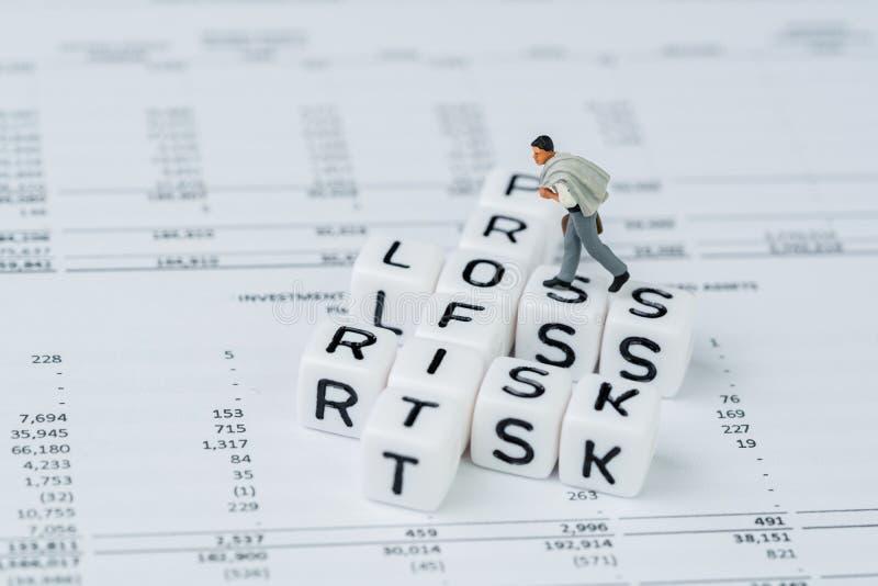 Risk, vinst och förlust i investeringbegreppet, miniatyraffärsman som går på det lilla vita kubkvarteret med alfabet med korsorde fotografering för bildbyråer