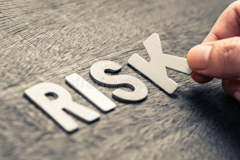 RISK WOOD LETTERS. Hand place wood letters for RISK word stock photography