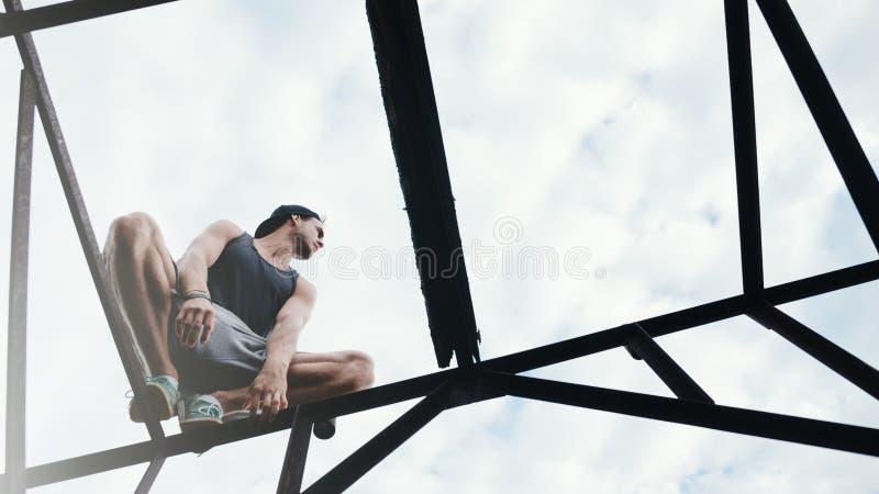 Riskabel man som balanserar och sitter på konstruktion för hög metall arkivfoton