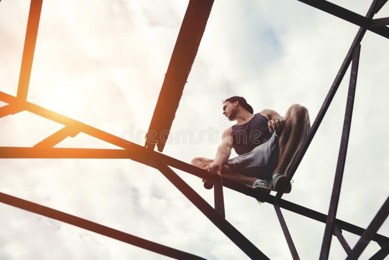 Riskabel modig man som balanserar och sitter på konstruktion för hög metall royaltyfria bilder