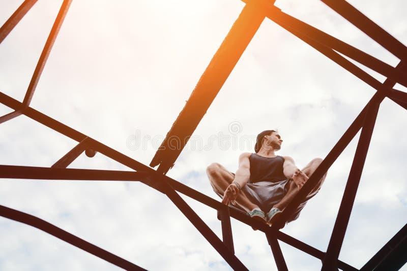 Riskabelt mansammanträde på konstruktion för hög metall royaltyfri fotografi