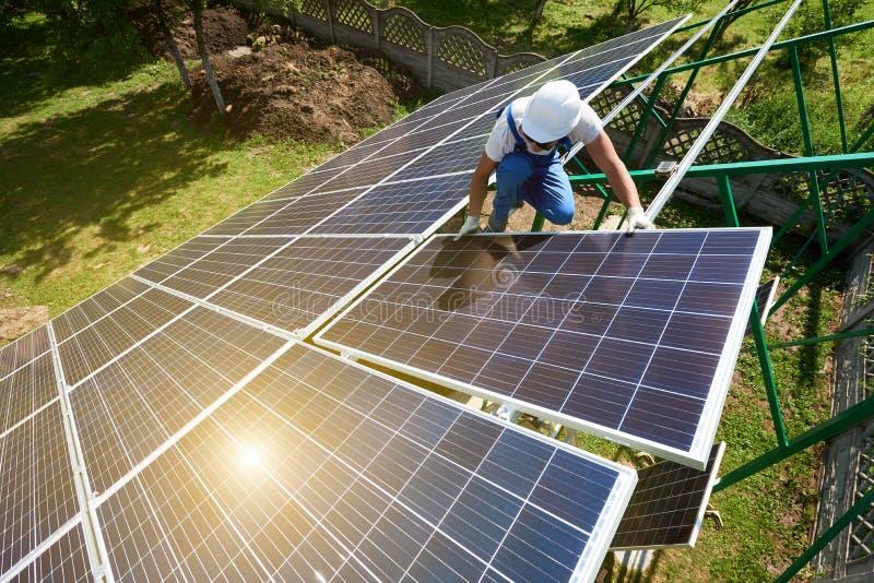 Riskante Arbeit: Befestigung von Solarbatterien an der grünen metallischen Karkasse stockbild
