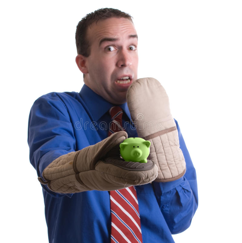 Risky Investment. Concept image a risky investment featuring a businessman holding a small piggy bank with oven mitts, isolated against a white background royalty free stock photos