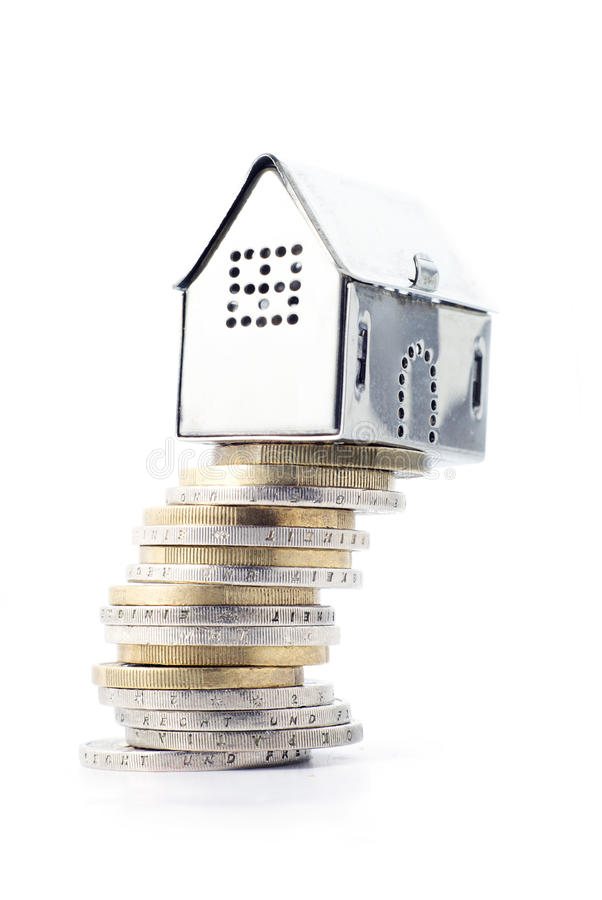 Risky real estate investment, small silver house on a slanted st. Concept image for risky real estate investment, small silver house on a slanted stack of coins royalty free stock images