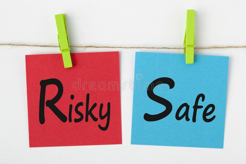 Risky or Safe Concept. Risky or Safe written on color notes with wooden pinch on white background. Business Concept stock images