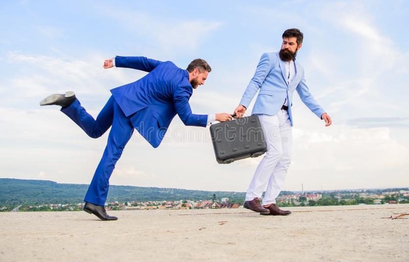 Risky transaction. Businessman takes away briefcase from business partner. Fraud and extortion concept. Men suits stock photos