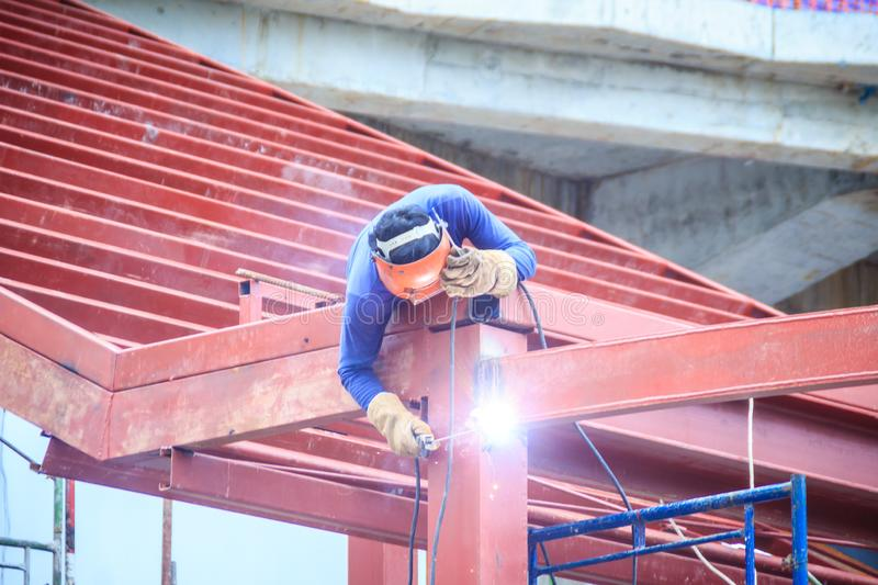 Risky welder while climbing and welding on top of the steel roof structure work at the building construction site. Skilled worker royalty free stock photography