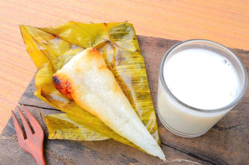 Riso appiccicoso aperto del dessert tailandese avvolto in foglia della banana con latte immagini stock libere da diritti