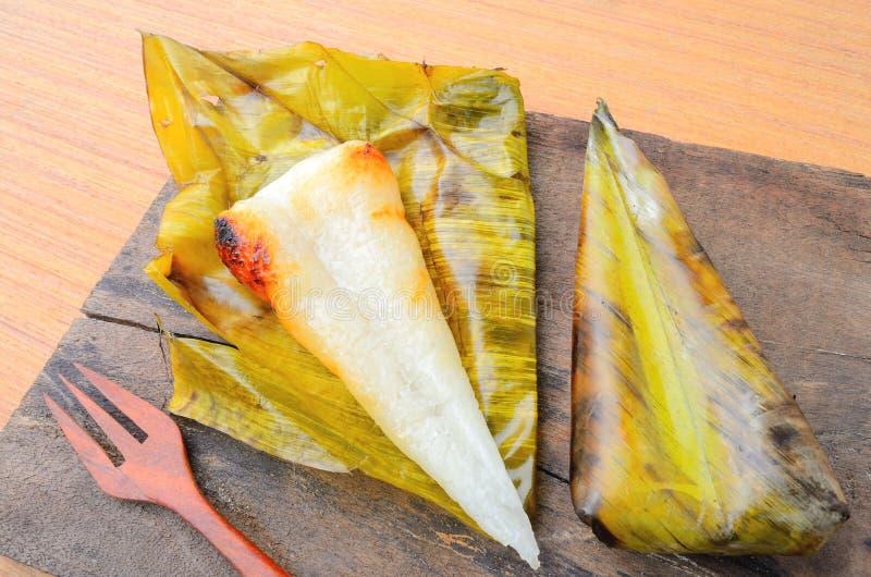Riso appiccicoso aperto del dessert tailandese avvolto in foglia della banana su fondo di legno immagine stock