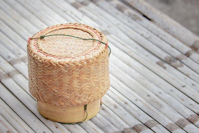 Riso appiccicoso del canestro di vimini sul bambù delle assi fotografia stock