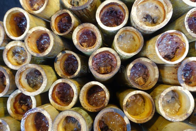 Riso appiccicoso dolce arrostito con il fillin del seme e del latte di cocco in bambù Fuoco selettivo fotografia stock