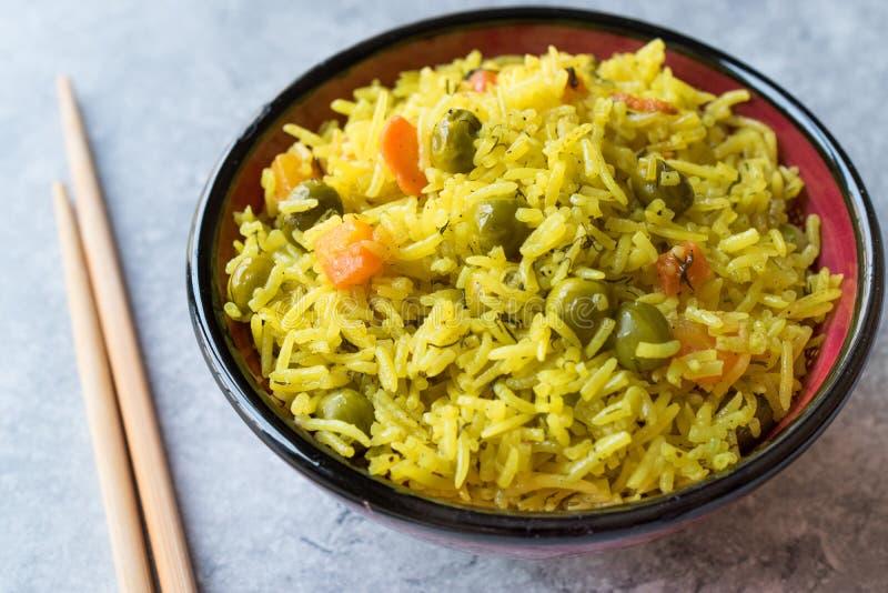 Riso basmati dello zafferano giallo con curcuma e verdure Pilav o pilaf in ciotola con i bastoncini immagini stock