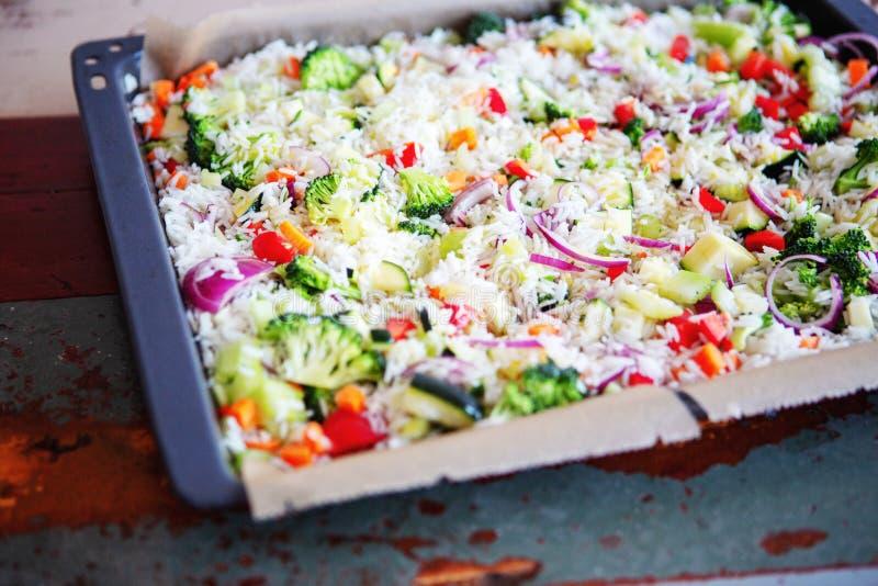 Riso bianco con i broccoli, le cipolle, lo zuccini e la paprica rossa sul tra fotografia stock