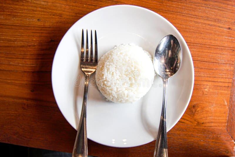 Riso bianco dell'alimento tailandese nel piatto con il cucchiaio d'argento due sulla tavola di legno fotografie stock libere da diritti