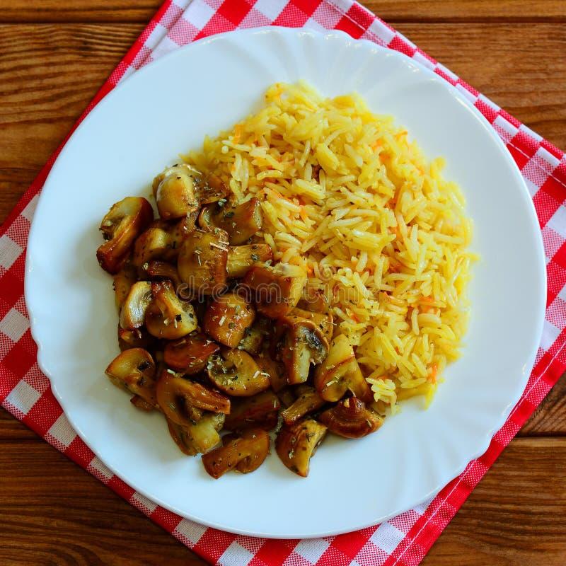 Riso casalingo con i funghi Riso cucinato Basmati con le carote ed i funghi fritti su un piatto bianco su una tavola di legno fotografia stock libera da diritti