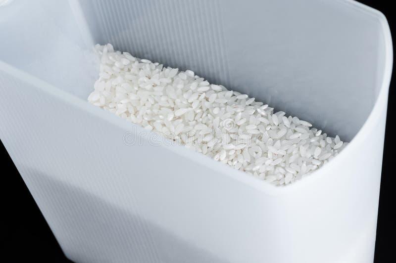 Riso crudo asciutto bianco nei contenitori di stoccaggio a casa su un fondo nero, isolato fotografia stock libera da diritti