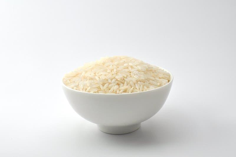 Riso crudo, riso del gelsomino, riso del Mali, riso tailandese del gelsomino in una ciotola bianca ceramica su fondo bianco fotografia stock