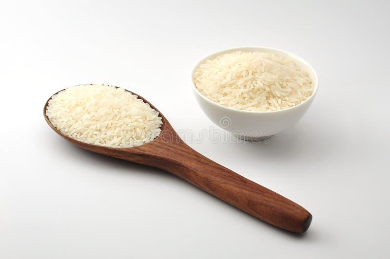 Riso crudo, riso del gelsomino, riso del Mali, riso tailandese in una siviera di legno, ciotola bianca del gelsomino ceramica su  fotografia stock