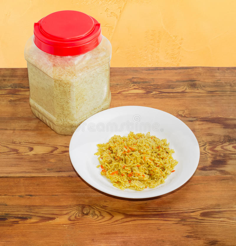 Riso cucinato sul piatto e riso crudo in recipiente di plastica fotografie stock