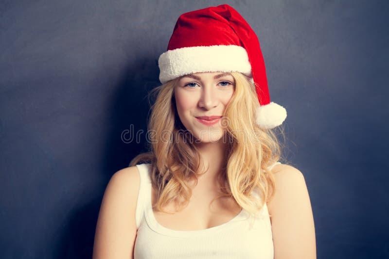 Riso da mulher do Natal Modelo de forma bonito do Xmas em Santa Hat no fundo azul foto de stock