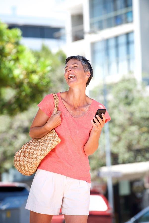 Riso de passeio da mulher mais idosa fora com telefone celular fotos de stock royalty free