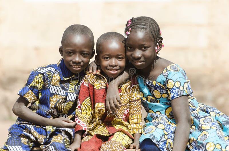 Riso de sorriso africano dos meninos e das meninas da família em África foto de stock